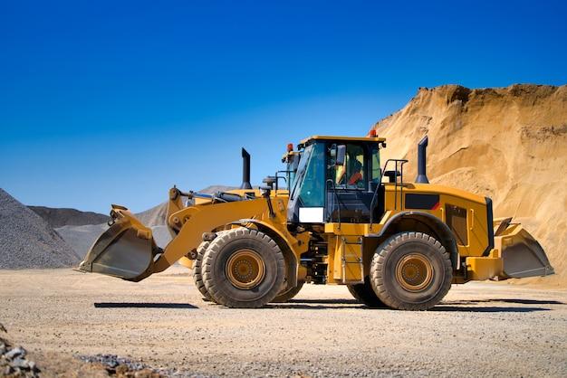 Yellow wheel skid-steer loader machine, loading gravel at construction