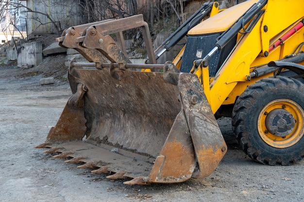 Желтый колесный трактор-экскаватор