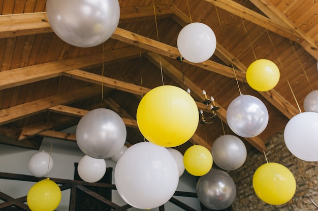 Yellow and white balloons on the ceiling in a wooden house.