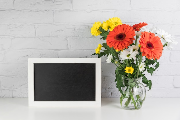Yellow and white chamomile with red gerbera flowers in the vase near the black frame on desk