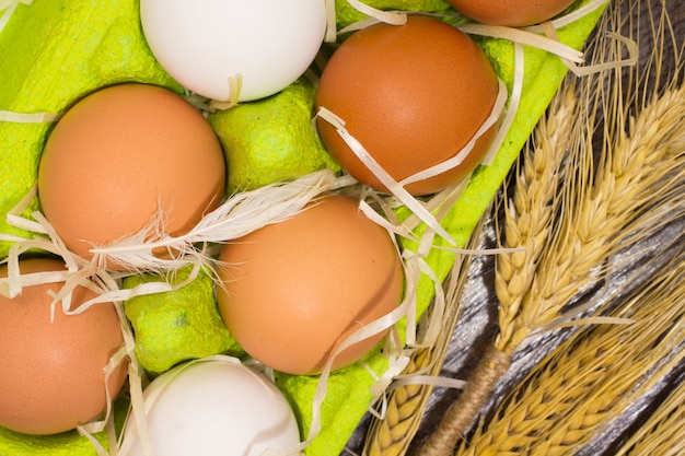 Yellow and white eggs in the box, chicken pen and wheat closeup