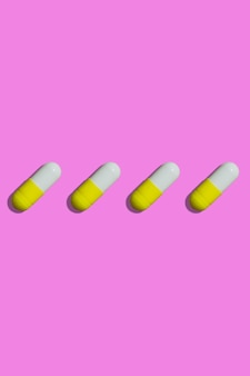 Yellow and white pills on a pink background top view