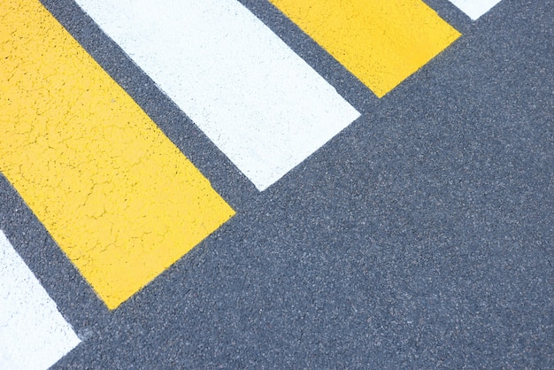 Yellow and white stripes of pedestrian crossing are painted on asphalt background