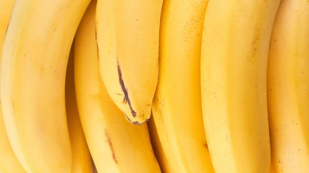 黄色のバナナ全体が背景をクローズアップ