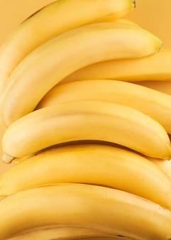 노란색 전체 바나나는 배경을 닫습니다.