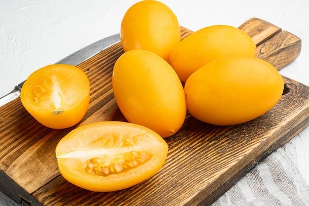 흰색 돌 테이블 배경에 슬라이스 세트가 있는 노란색 전체 토마토