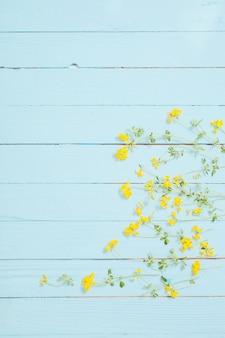 青い木製の背景に黄色の野生の花