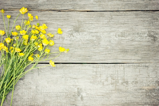 Yellow wildflowers on wooden background. the concept of yellow
