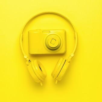 노란색 무선 헤드폰과 노란색 배경에 노란색 카메라. 단색화. 창의적인 이미지. 플랫 레이.