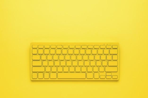 Желтая беспроводная клавиатура на ярко-желтом фоне. монохромное изображение офисных принадлежностей.