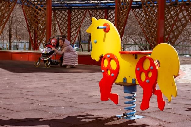 Желтая с красными качелями весенняя лошадь-игрушка для детей на детской площадке мама с младенцем в коляске
