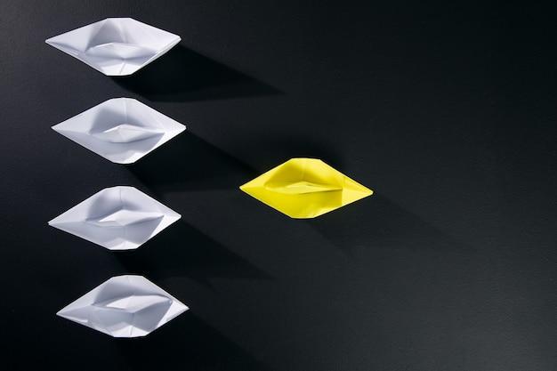 검은 색 표면에 흰 종이 보트와 노란색