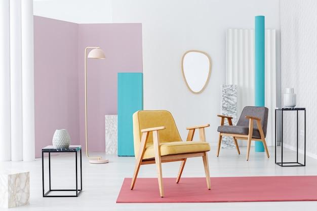 壁に鏡が付いているパステルレトロなリビングルームのインテリアのピンクの敷物に黄色の木製アームチェア