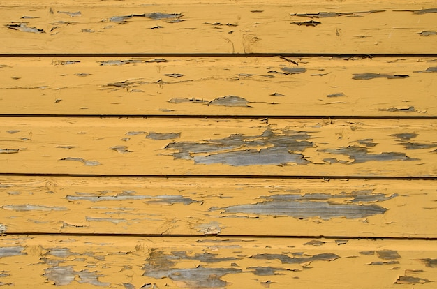 Yellow wooden background with peeled pieces of old paint.