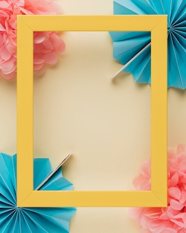 Yellow wooden border photo frame on paper flower over beige backdrop