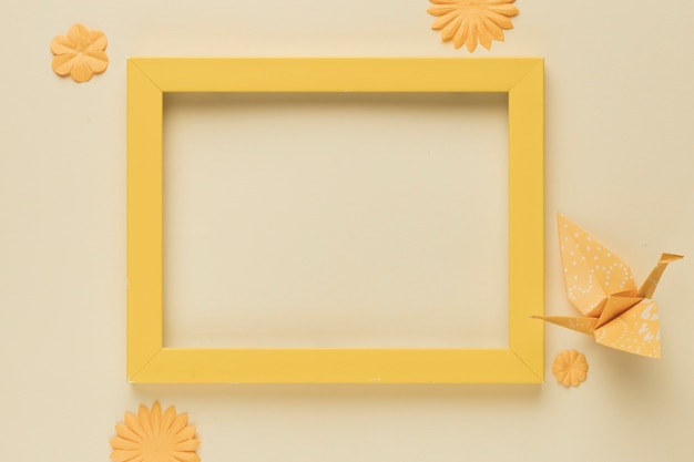 Yellow wooden frame with paper bird and flower cutout