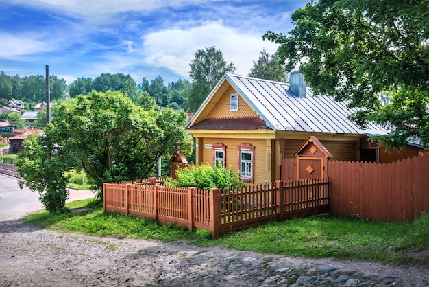 Желтый деревянный дом на улице спуск горы свободы в плёсе среди зелени летних деревьев. надпись: улица спуск с горы свободы