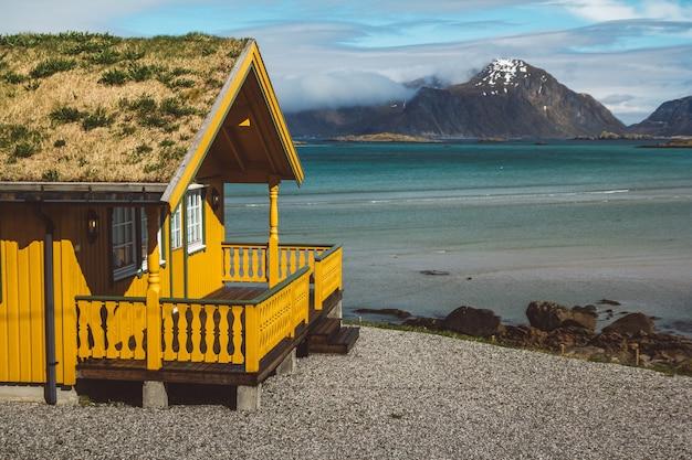 바다와 산을 배경으로 지붕에 이끼가 있는 노란색 목조 주택.