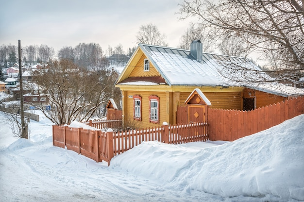 푸른 하늘 아래 겨울 날에 비추어 plyos의 산 중턱에 노란색 목조 주거용 건물