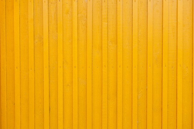 노란색 나무 얼룩 무늬 벽 배경 질감. 목조 주택의 벽은 노란색으로 칠해져 있습니다. 수직 노란색 나무 렌더링 벽 배경을 그렸습니다. 벽 디자인