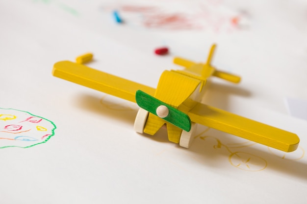 Yellow wooden toy plane on the white background with kids drawings