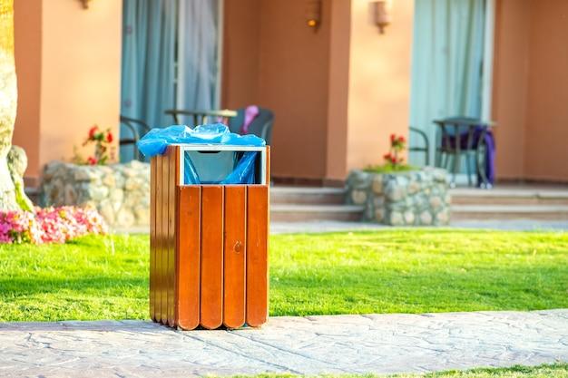 Желтый деревянный мусорный бак на улице на тротуаре в парке. контейнер для мусора на улице снаружи.