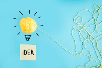 Yellow wool idea light bulb on blue background with idea text on sticky note