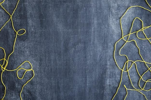 Yellow wool string on blank chalkboard