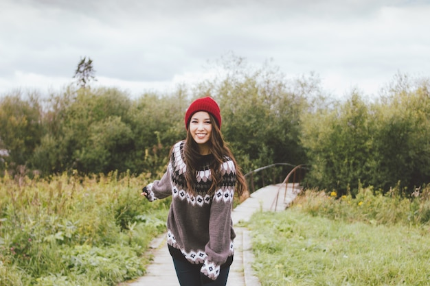 秋の公園でyellredowの帽子とニットのセーターを着ている美しいアジアの少女
