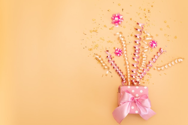 Yelow gift box with various party confetti, streamers, noisemakers and decoration on a orange background.