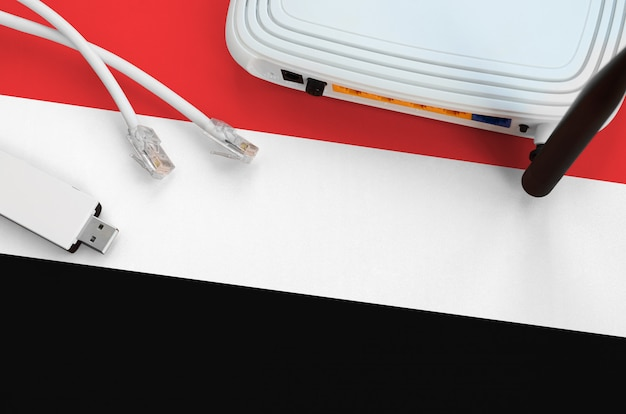 Йеменский флаг изображен на столе с интернет-кабелем, беспроводным usb-адаптером wi-fi и маршрутизатором. концепция интернет-связи