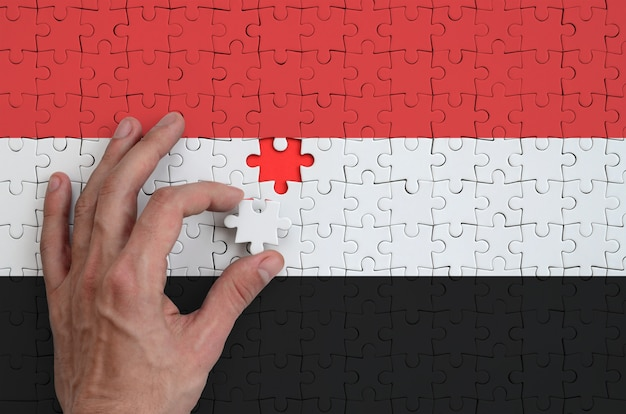 Yemen flag  is depicted on a puzzle, which the man's hand completes to fold