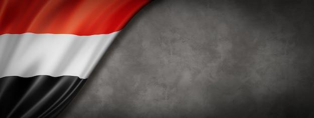 コンクリートの壁のバナーにイエメンの国旗