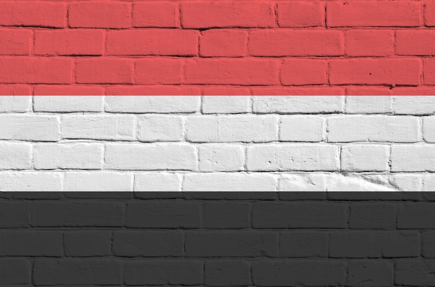 Yemen flag in paint colors on old brick wall