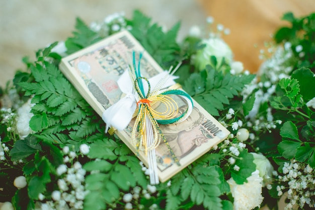 Yen banknotes with beautiful ribbon place on green leafs and white flowers.