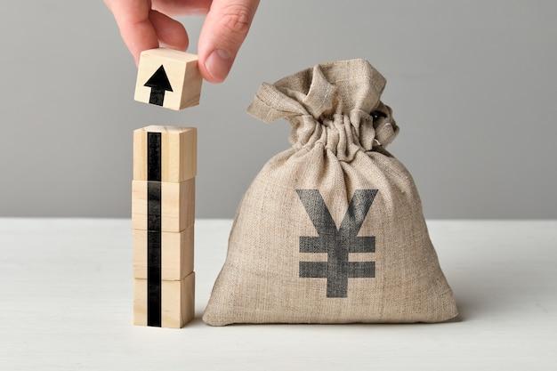 Концепция роста валюты иены с мешком стрелки и денег вверх.