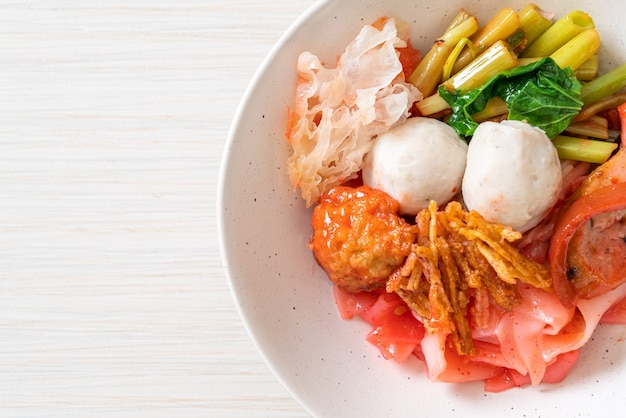 (yen-ta-four) - dry thai style noodle with assorted tofu and fish ball in red soup - asian food style