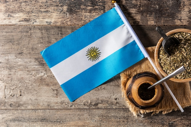 Yerba mate tea and argentina flag on wooden table with copy space. traditional argentinian beverage