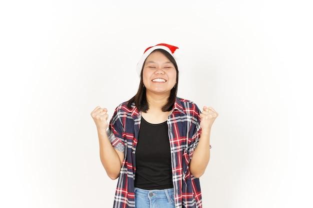はい、聖霊降臨祭で隔離の赤い格子縞のシャツとサンタの帽子を身に着けているアジアの女性の興奮したジェスチャー