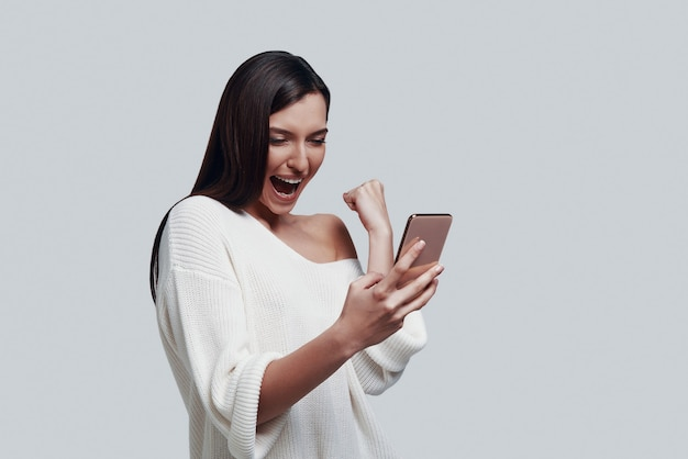 Yes! attractive young woman using smart phone and gesturing while standing against grey background
