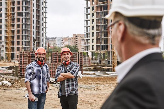 예, 두 명의 쾌활한 젊은 건축업자로 구성된 보스 전문 팀이 건설 현장에 서 있습니다.