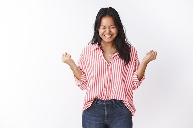 はい、努力はついに成功をもたらしました。勝利を祝って勝利を収め、握りこぶしを握りしめ、幸せと笑顔から目を閉じて満足している幸せな若いポリネシアの女の子の肖像画