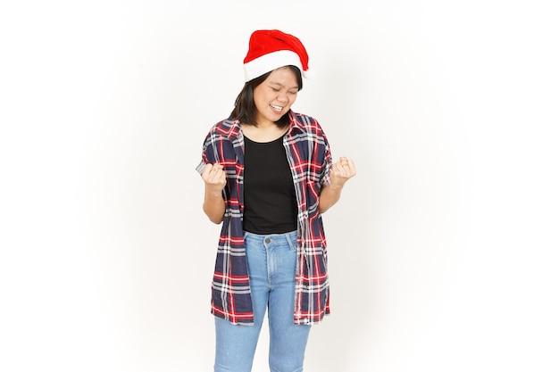 예 빨간 격자 무늬 셔츠와 흰색 절연 산타 모자를 입고 아름 다운 아시아 여자의 흥분된 제스처