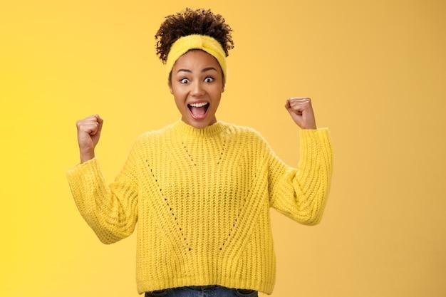 はい、ついに私の賞を受賞しました。勝利の達成を祝う興奮した驚きの面白がってアフリカ系アメリカ人の女の子は、黄色の背景に立って、成功を勝ち取って大声で叫んでいる残りの拳を笑顔で応援しています。