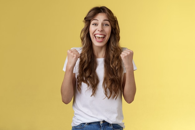 Yes finally success. cheerful enthusiastic happy girl pump fists lift hands victory joy celebration gesture smiling broadly relieved winning lottery amused stand yellow background triumphing.