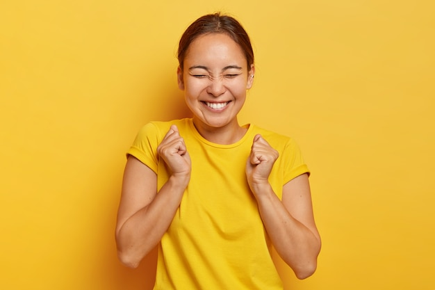 Yes, finally success! joyful korean girl clenches fists with triumph, closes eyes from happiness and joy, has toothy smile, wears casual outfit, isolated on yellow wall, triumphs victory