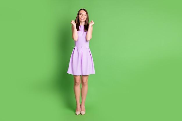 はい。全身写真率直で嬉しい大喜びの女の子女性が拳を上げて目を閉じて宝くじに勝つとは信じられない割引賞品を着る紫色のドレスベージュの靴孤立したパステルグリーンの色の背景