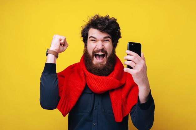 예 ! 팔짱을 끼고 축하하고, 빨간 스카프를 두르고, 노란색 배경 위에 스마트폰을 들고 있는 잘생긴 수염 난 남자