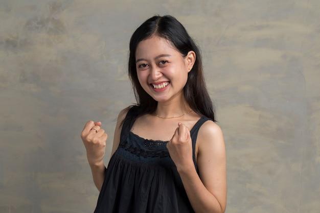 예. 행복 한 아시아 여자 주먹을 떨고 승자 제스처를 만들기