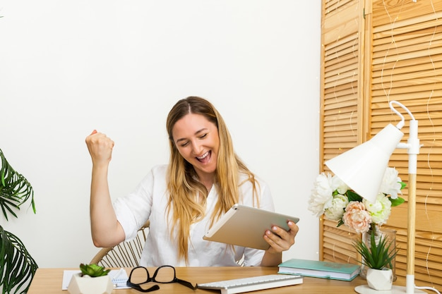 Да. счастливый взволнованная женщина на рабочем месте дома, торжествуя с поднятыми руками